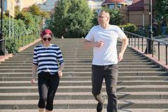 Outdoor portrait of running mature couple. Man and woman of 40 years old running up the stairs. Outdoor portrait of running mature couple. Man and women of 40 royalty free stock photography