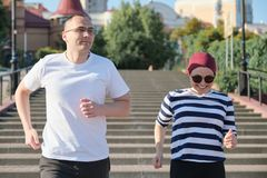 Outdoor portrait of running mature couple. Man and woman of 40 years old running up the stairs. Outdoor portrait of running mature couple. Man and women of 40 stock photos