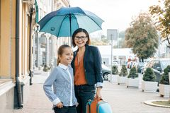 Outdoor portrait of smiling mother and daughter under an umbrella. Mother and girl with backpack on the way to school stock images