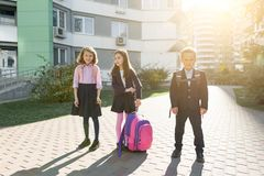 Outdoor portrait of smiling schoolchildren in elementary school. Group of kids with backpacks are having fun, talking. Education, friendship, technology and royalty free stock photos