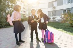 Outdoor portrait of smiling schoolchildren in elementary school. Group of kids with backpacks are having fun, talking, reading a. Book. Education, friendship stock image