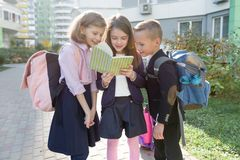 Outdoor portrait of smiling schoolchildren in elementary school. Group of kids with backpacks are having fun, talking, reading a. Book. Education, friendship stock photography