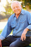 Outdoor Portrait Of Smiling Senior Man. Sitting Down Looking At Camera Royalty Free Stock Images