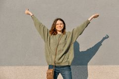 Outdoor portrait of smiling teen girl with arms raised up, gray sunny wall background, emotion of happiness and joy stock images