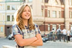 Outdoor portrait of smiling teenager girl 12, 13 years old on city street, girl with folded hands, copy space stock photos