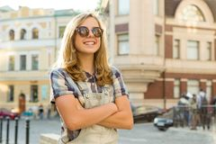 Outdoor portrait of smiling teenager girl 12, 13 years old on city street, girl with folded hands, copy space royalty free stock photography