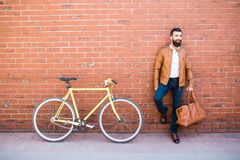 Outdoor portrait of standing bearded hipster with bag in hand near fixed bicycle against brick wall. Portrait of standing bearded hipster with bag in hand near Stock Images