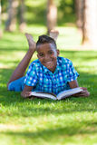 Outdoor portrait of student black boy reading a book. African people Stock Photos