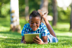 Outdoor portrait of student black boy using a tactile tablet Royalty Free Stock Photos