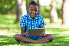 Outdoor portrait of student black boy using a tactile tablet Stock Photo