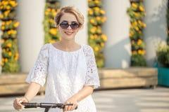 Stunning girl on city street on kick scooter. Enjoying sunny day. Wearing sunglasses, short shorts. Outdoor portrait of stunning girl on city street on kick stock photo