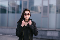 Outdoor portrait stylish girl brunette dressed in black and wearing sunglasses on a background of gray city background. Outdoor portrait of stylish and beautiful Royalty Free Stock Image