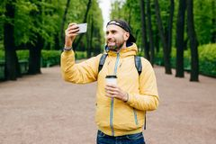 Outdoor portrait of stylish man with stubble beard wearing yellow anorak and holding backpack and takeaway coffee making selfie wi royalty free stock photography