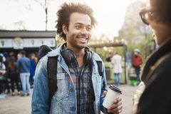 Outdoor portrait of stylish upbeat african-american male with bristle and afro hairstyle holding cup of coffee and. Smiling broadly while talking to attractive Stock Photos