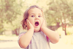 Outdoor portrait of surprised cute child girl on natural backgro Royalty Free Stock Images