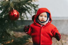 Outdoor portrait of sweet little 1 year old baby girl playing with Christmas tree Royalty Free Stock Photography