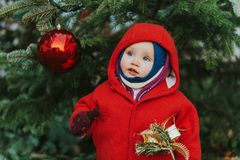 Outdoor portrait of sweet little 1 year old baby girl playing with Christmas tree Royalty Free Stock Images
