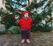 Outdoor portrait of sweet little 1 year old baby girl playing with Christmas tree Stock Photo