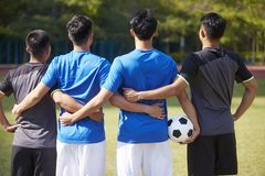 Rear view of a team of asian soccer players. Outdoor portrait of a team of young asian soccer football players, rear view royalty free stock images
