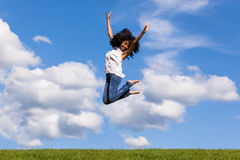 Outdoor portrait of a teenage black girl jumping o Royalty Free Stock Photo