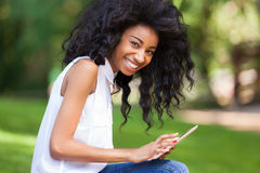 Outdoor portrait of a teenage black girl using a tactile tablet Stock Image