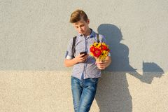 Outdoor portrait of teenage boy with bouquet of flowers, gray wall background, copy space. Outdoor portrait of teenage boy with bouquet of flowers, gray wall Royalty Free Stock Photo