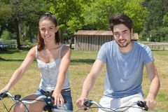 Outdoor portrait teenage couple riding bicycles in nature Royalty Free Stock Photo