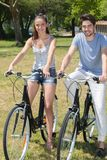 Outdoor portrait teenage couple riding bicycles in nature Royalty Free Stock Photos