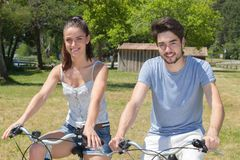 Outdoor portrait teenage couple riding bicycles in nature Stock Photos