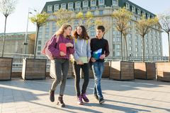 Outdoor portrait of teenage students with backpacks walking and talking royalty free stock image