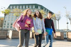 Outdoor portrait of teenage students with backpacks walking and talking stock image