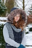 Cheerful teenager girl in winter cloths and fur hood. Outdoor portrait of a teenager girl in winter cloths Royalty Free Stock Image