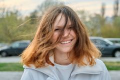 Outdoor portrait of teenager girl 15 years old, girl smiling with long brown hair in white jacket stock photo