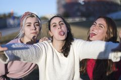 Outdoor portrait of three friends fun girls taking photos with a smartphone at bright sunset royalty free stock photography