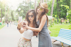 Outdoor portrait of three friends take selfie with smartphone Royalty Free Stock Images