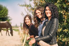 three women standing and smiling next to the wooden fence stock image