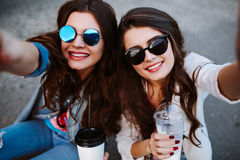 Outdoor portrait of two best friends making selfie. 2 glamorous women photographing themselves,smiling,denim outfit. Royalty Free Stock Photography