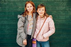 Outdoor portrait of two cute little teen girls wearing warm jackets. Posing against green background, fashion for children Stock Images