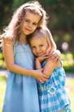 Outdoor portrait of two embracing cute little girls Stock Image