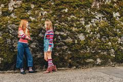 Outdoor portrait of two funny preteen girls. Wearing denim shorts, stripe roll neck pullovers and long socks, posing against moss wall, fashion for teens Royalty Free Stock Photos