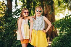 Outdoor portrait of two funny preteen girls. Wearing sunglasses Stock Image