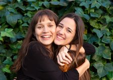 Outdoor portrait of two happy sisters in a park Stock Photos