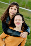 Outdoor portrait of two happy sisters relaxed Royalty Free Stock Image