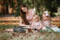 Outdoor portrait of two little girl is reading a book on the grass with mother stock photo
