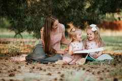 Outdoor portrait of two little girl is reading a book on the grass with mother royalty free stock photography