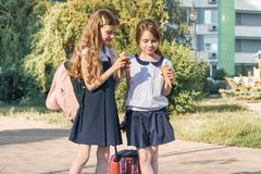 Outdoor portrait of two little schoolgirls with backpacks in school uniforms, smiling and eating ice cream stock photo