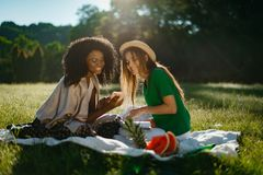 Outdoor portrait of two multi-ethnic girl friends spending time together on picnic on the sunny meadow. The young. Smiling african girl is showing something on Royalty Free Stock Photos