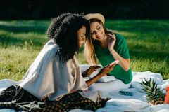 Outdoor portrait of two multi-race happy girl friends watching something on the mobile phone uring their picnic on the. Meadow Royalty Free Stock Images