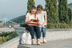 Outdoor portrait of two young beautiful girls students with backpacks, books. Girls talking, looking into a book, urban background.  royalty free stock photos