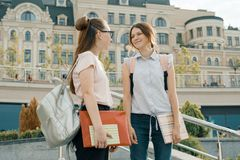 Outdoor portrait of two young beautiful girls students with backpacks and books talking and smiling, urban background.  stock image